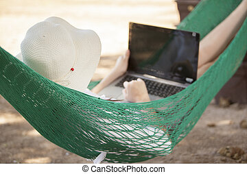 Telecommuting in a hammock - Young woman using a laptop...