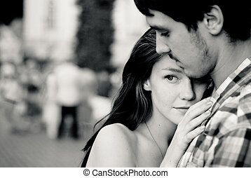 Young couple embracing tenderly in crowd - Young couple man...
