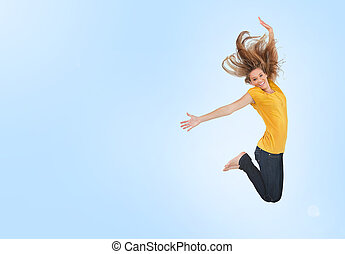 Pretty young woman jumping for joy on blue background