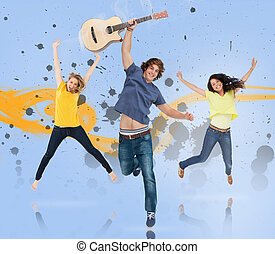 Young man with guitar and two girls jumping for joy with...