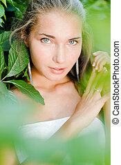 Young beautiful woman portrait among green leaves of...