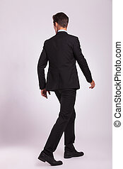 back view of business man walking - back view of a young...