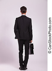 business man and brief, back view - back view of a young...