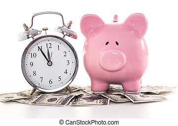 Pink piggy bank beside alarm clock on dollars on white...