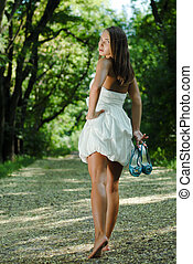 Young beautiful woman walking in green park with shoes in...