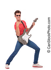 guitar man in classic rock pose - casual young man standing...