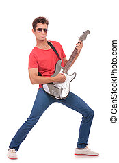 guitarist plays & looks at you - casual young man playing...