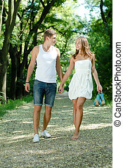 Young happy couple walking in green park holding hands -...