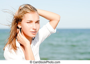 Young beautiful woman sitting by blue sea on windy summer...