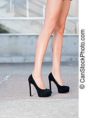 Beautiful silky legs in black high heels shoes outdoor...
