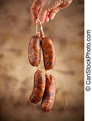 Raw sausage with hand on beige background