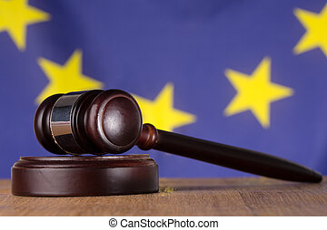 Gavel resting on sound block with european union flag in...