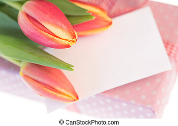 Pink and yellow tulips resting on pink wrapped present with...