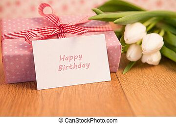 Pink wrapped present with bunch of white tulips and happy birthday card on wooden table