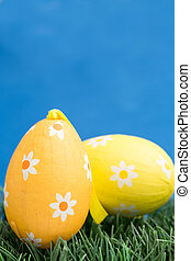 Two easter eggs on grass on blue background