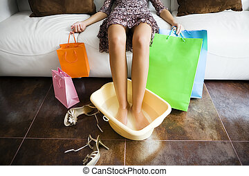 shopping - Woman soaking feet in water after long day...
