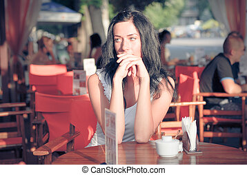 Young beautiful woman sitting on patio cafe and waiting -...