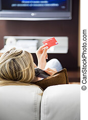 shopping - Young woman watching tv and using credit card