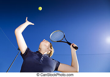 tennis - blond woman playing tennis, about to hit the ball....
