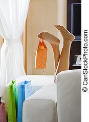 shopping - Young woman\\\'s legs dangling shopping bag