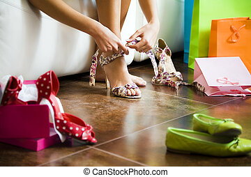 shopping - Young woman trying on high heel shoes