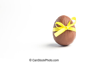 Chocolate easter egg in a yellow ribbon on white background...