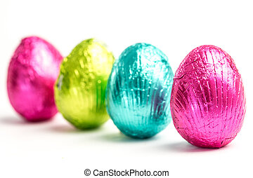 Four easter eggs in a row wrapped in a colourful foil