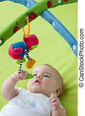 Baby looking up at a mobile toy - Baby grabbing a hanging...