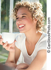 Young happy woman having morning cup of coffee by the window