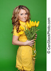 Happy smiling girl with spring-flowering yellow tulips...