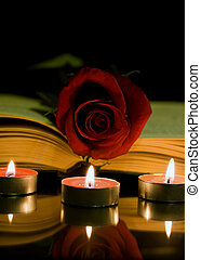 Red rose and book - Open book and a red rose and candle on a...