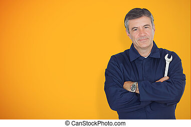 Mature mechanic standing in front of yellow background while...