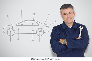 Mature mechanic standing next to car diagram while looking...