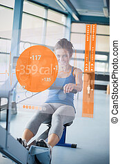 Front view of an attractive girl on rowing machine with...