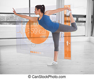 Brunette in yoga pose with futuristic interface next to her...