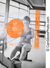 Front view of a girl on rowing machine with futuristic...