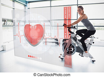 Young girl doing exercise bike with futuristic interface...