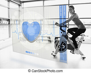 Young attractive smiling girl doing exercise bike with...