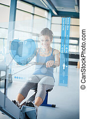 Young girl doing rowing machine with futuristic interface -...