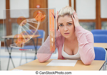 Blonde woman thinking hard while studying on interface with...