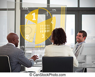Business people using yellow pie chart interface in a...