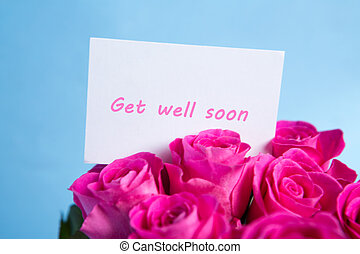 Bouquet of pink roses with get well soon card on blue...