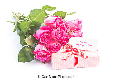 Bouquet of pink roses next to a gift with a happy birthday...