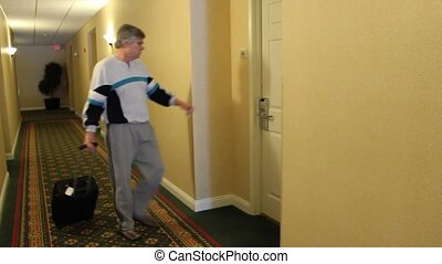man enters motel room - guest enters a motel room with a...