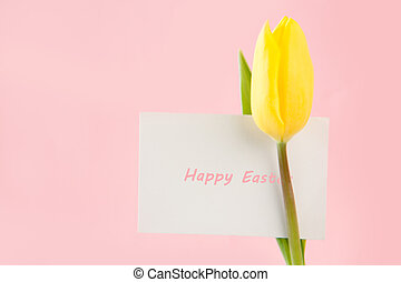 Yellow tulip with a Happy Easter card written in pink on a...