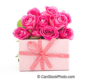 Bouquet of pink roses next to a pink gift on a white...