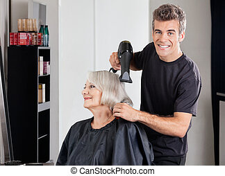 Male Hairdresser With Dryer Setting Customer's Hair -...