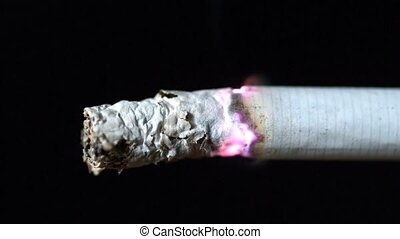 Cigarette burning on black background close up in slow...