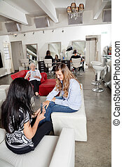 Customer Having Manicure At Parlor - Mid adult female...