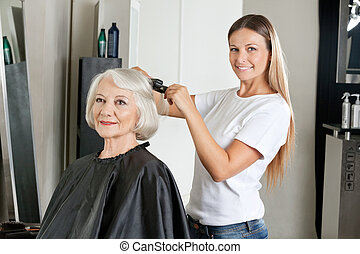 Hairdresser Ironing Woman's Hair - Portrait of female...